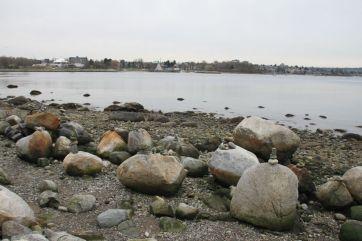 Someone goes along stacking rocks along the shore